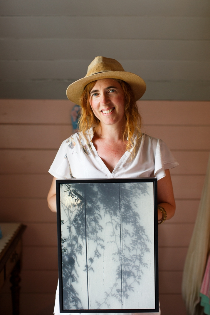 Woman in hat with photographic work in frame.