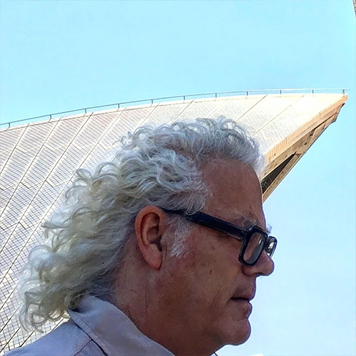Headshot of man with curly hair against Opera House sails.
