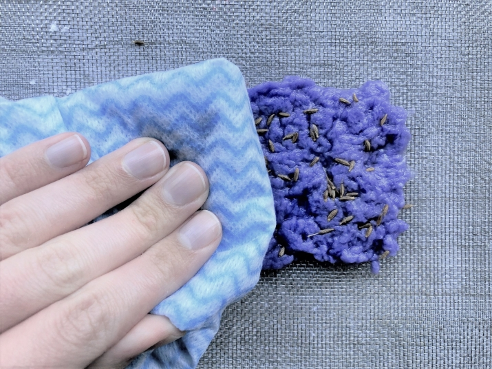 Wiping paper clump with blue cloth.