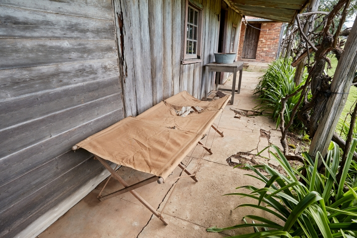 Cot on verandah, with greenery visible to right of image.