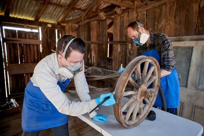 Two men wearing blue aprons and masks working on object inside wooden shed.