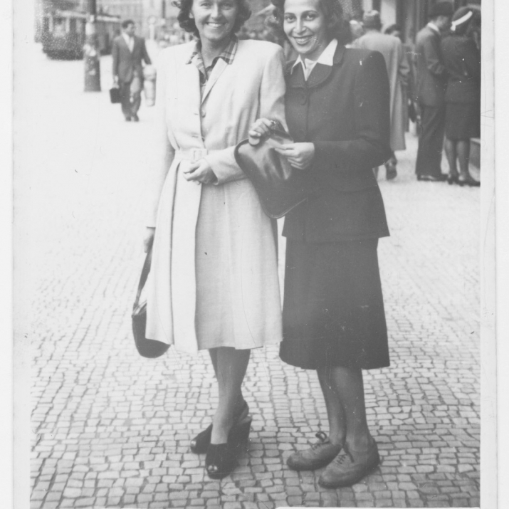 Black and white photo of two women in coats in street setting.
