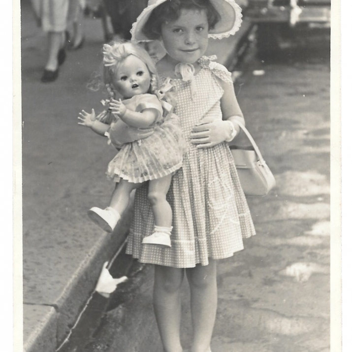 Black and white photo of little girl in hat with doll.