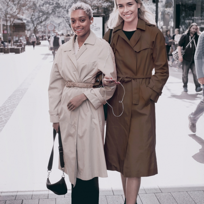 Two young women in coats in urban mall setting.