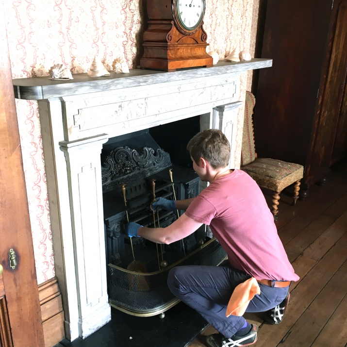 Person bending down to place fire tools inside fire place.