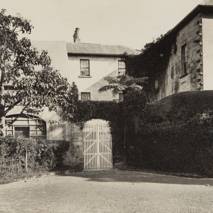Black and white photo of stone archway leading to house behind.