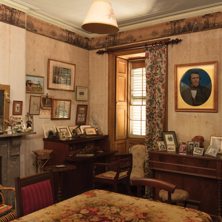Corner of room with harmonium and several framed photographs near window.