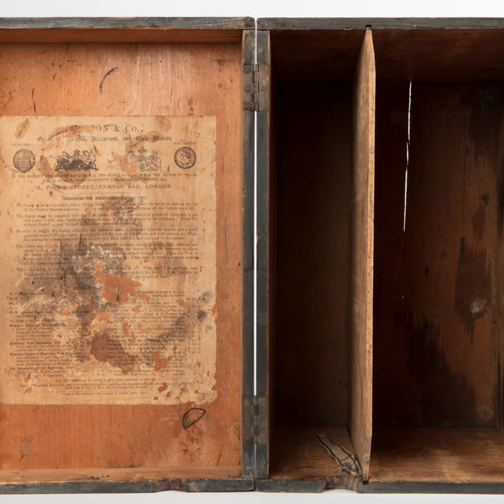 View inside timber case with paper notice pasted inside lid.