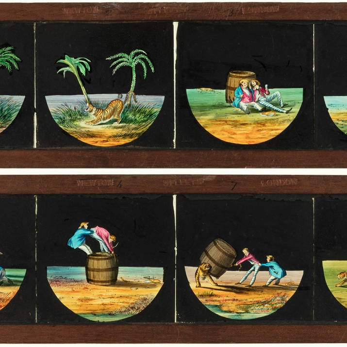 Two static, timber-framed glass slides for a magic lantern. These slides feature a sequence of individual hand-painted scenes of two men on a desert island with a tiger.