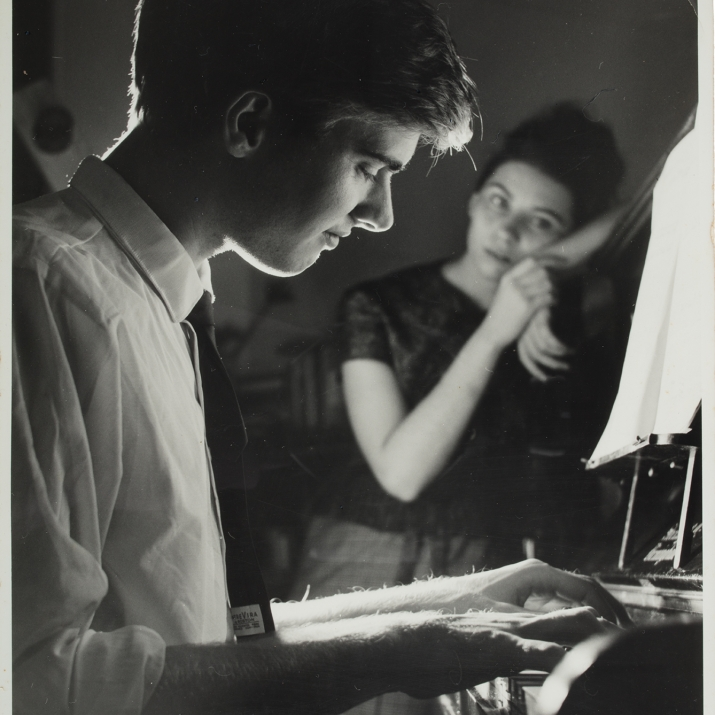 A black and white contemporary photograph of John Terry playing the piano. Caroline Terry (later Caroline Thornton) is shown in the background on right, leaning against the piano.