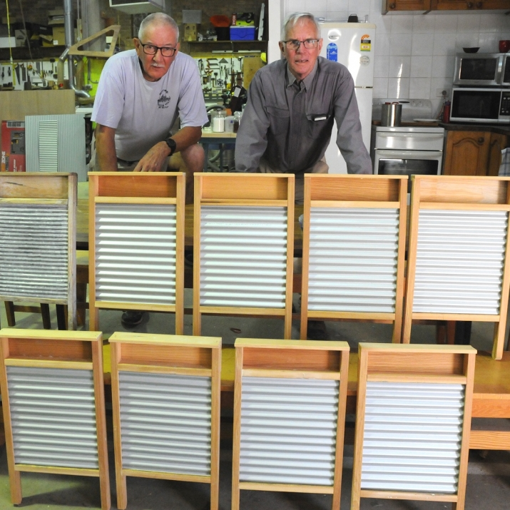 Two men with rows of completed wood and tin washboards.
