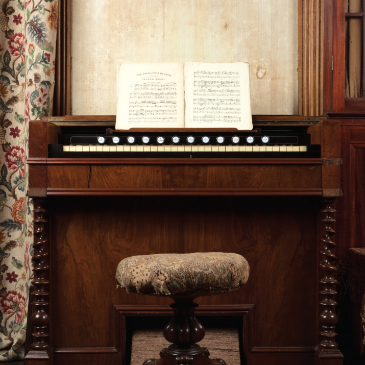 Harmonium viewed straight on, with stool and music book open on stand.