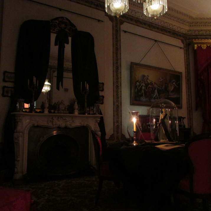 Room draped in black cloths with candles.