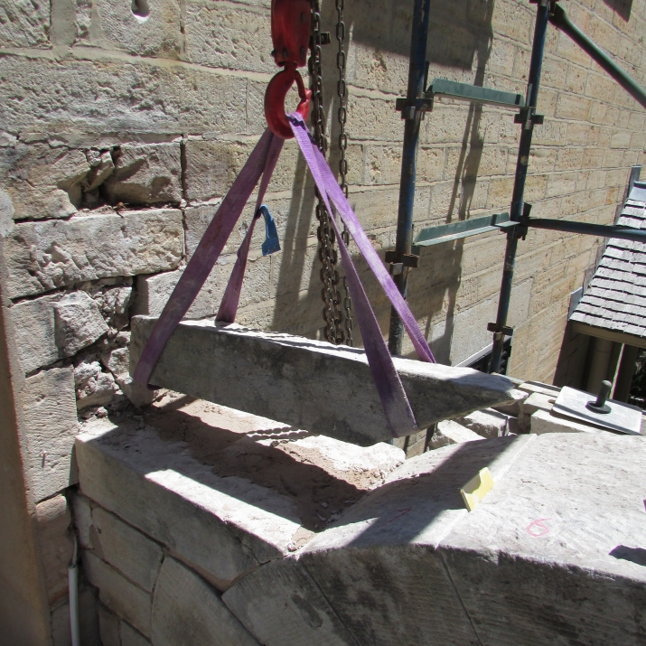 Pulley holdng stone above archway.
