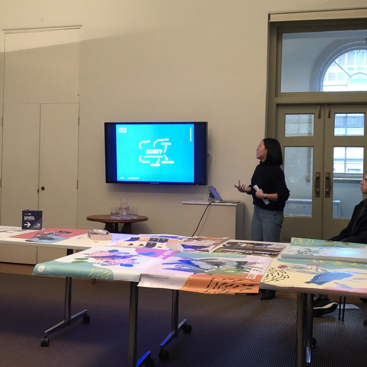 Interior shot of group presentations, with projector and physical materials in conference room setting.
