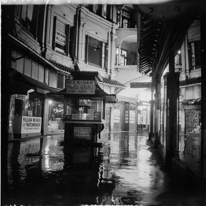 Black and white photo of interior of arcade with booth in centre.