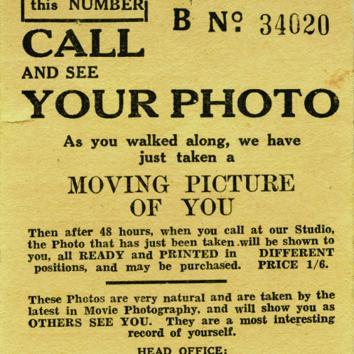 Yellow printed ticket with number to top right, with information about how to collect photo.