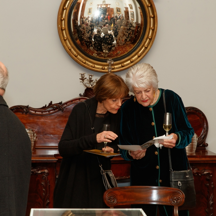 Two guests looking at a program at event.
