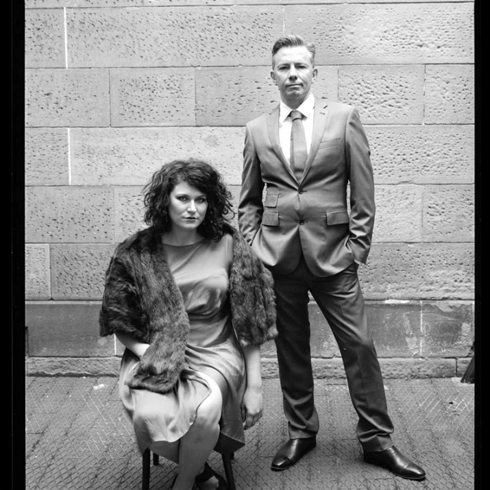 Black and white mugshot recreation photo with seated woman and man, standing.