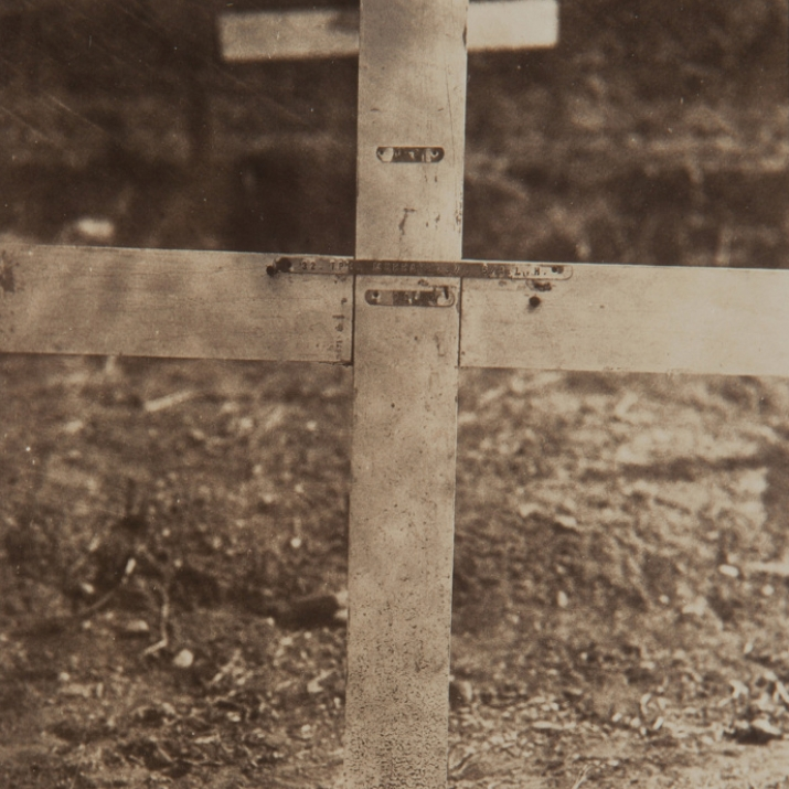 Cropped photograph to show detail of grave marker with metal strip attached.
