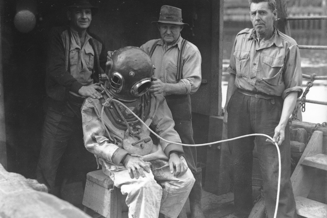 Man in diving suit with other men assisting.