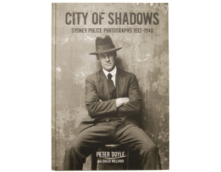 Book cover of City of Shadows with sinister character seated in chair.