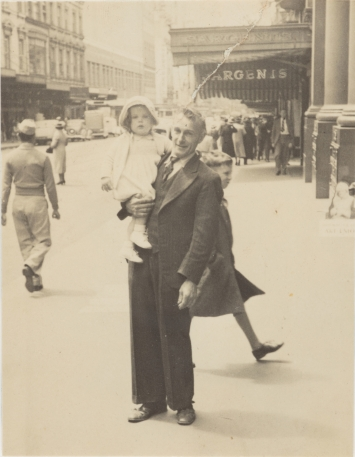 Black and white photo with yellowish tone of man in suit holding child in pale dress and shoes, standing in street.