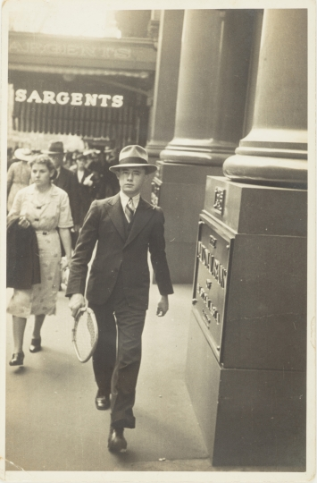 Black and white photo with yellowish tone of man in hat walking down street.
