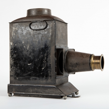 View of metal body of lantern with brass lens pointing right.