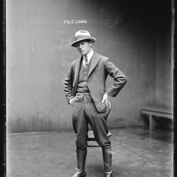Black and white mugshot of man standing with hat on.