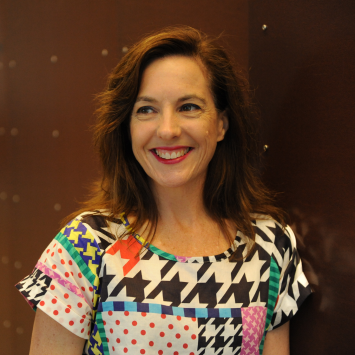 Portrait of woman smiling, wearing a patterned shirt.