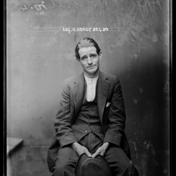 Single mugshot of seated hatless man.