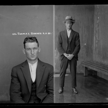 Dual mugshot in black and white; man seated and then man standing, with hat on.