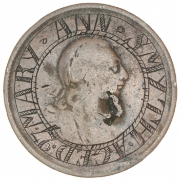 Coin with inscription engraved on it, with head in centre of coin.