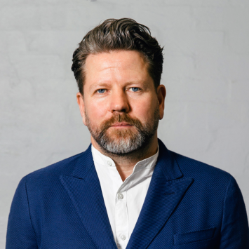 Portrait of bearded man in white shirt and blue suit jacket.