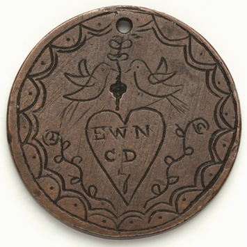 Coin with inscribed design and initials EWN and CD inside love heart.