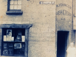 Hugo Youngein (Lyunggren) standing outside his 'cash grocer' at 64 Gloucester Street c1920s