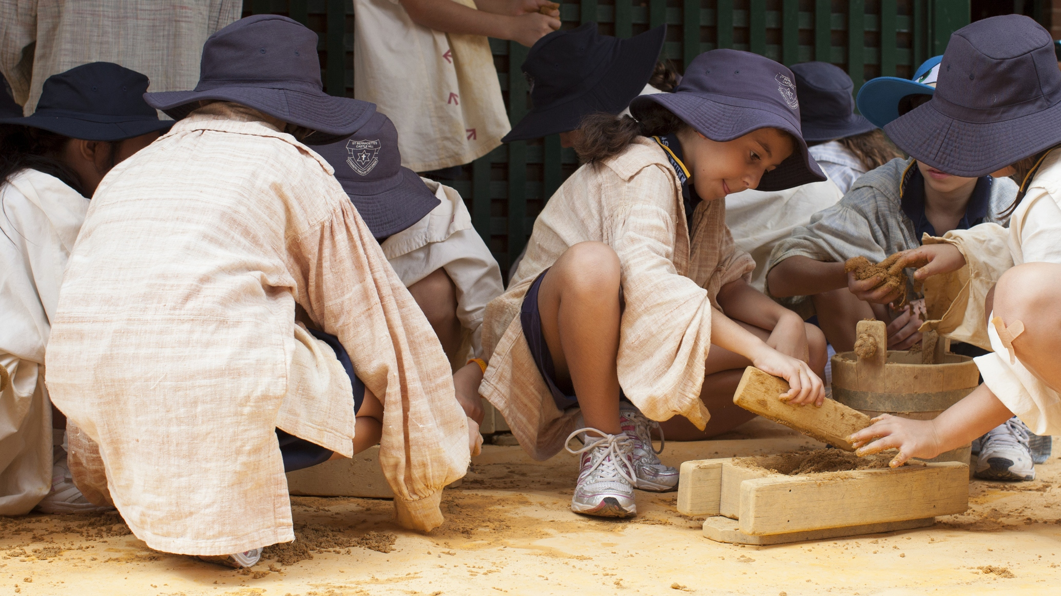 Children  dressed as convicts using reproduction brick making equipment to make sand bricks.