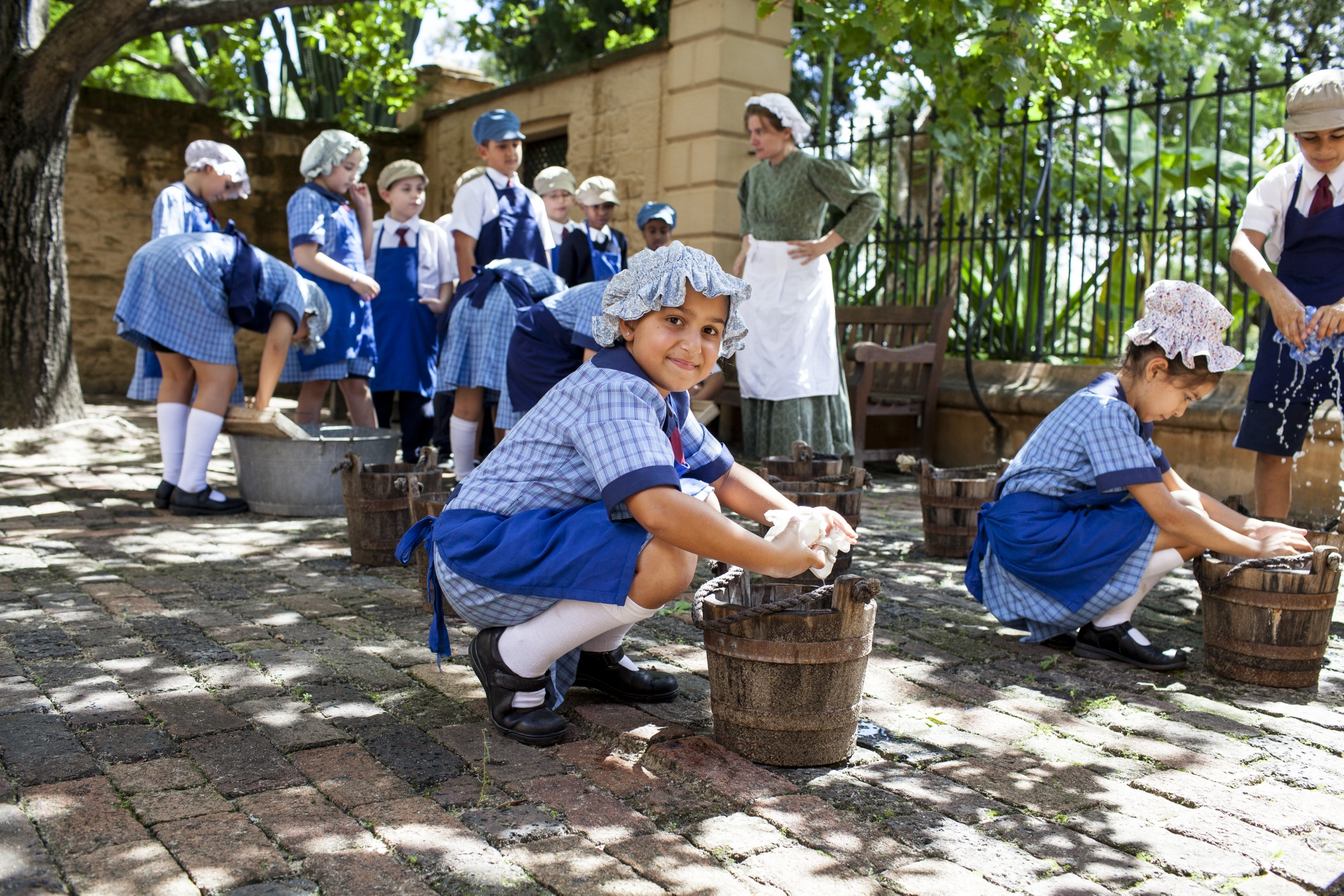 Students dressed up in stone courtyard with washing buckets and laundry.