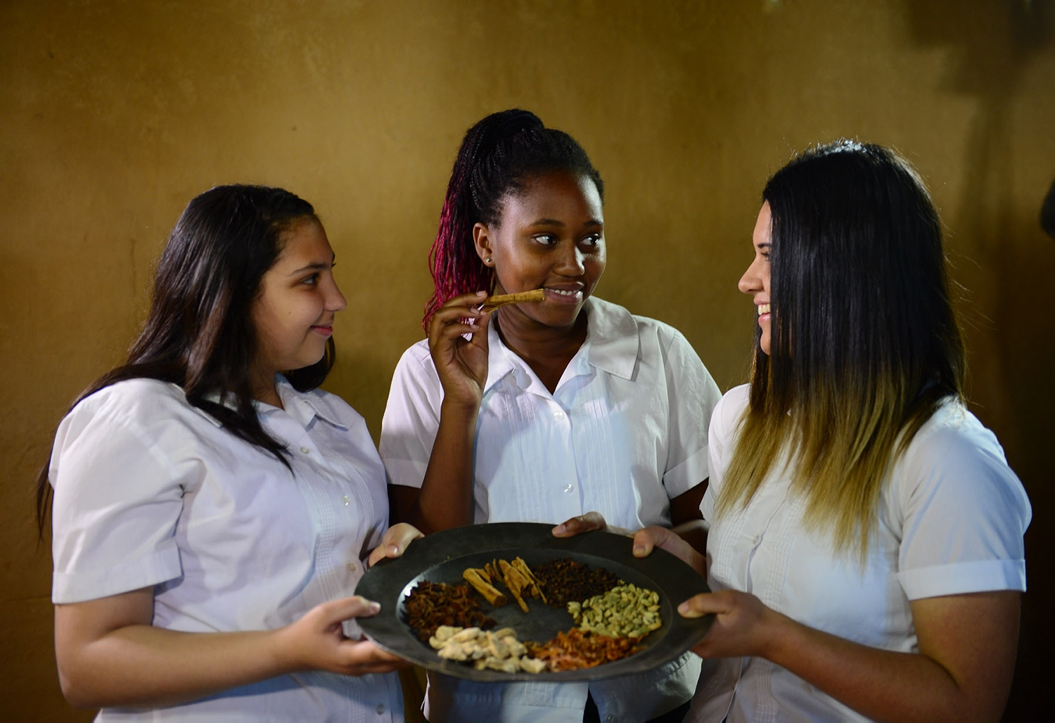 Three girls in white school shirts holding plate of various ingredients.