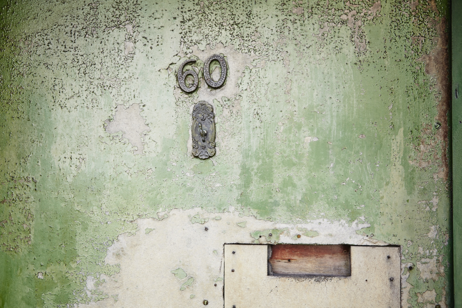 The number 60 on a faded green-painted surface.