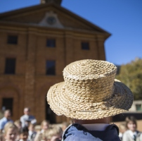 Child with straw hat in front of the Barracks.