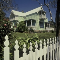 Exterior view of Meroogal, a two story green house. The sun is shining and the gardens look plush. There is a picket fence in the foreground.