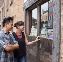 From left to right: Arnel Rodriguez and Natalie Webb looking in the window of the corner shop, 64 Gloucester Street, Susannah Place Museum, The Rocks, Sydney.