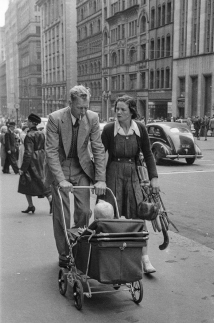 Black & white candid photo of people walking down city street.