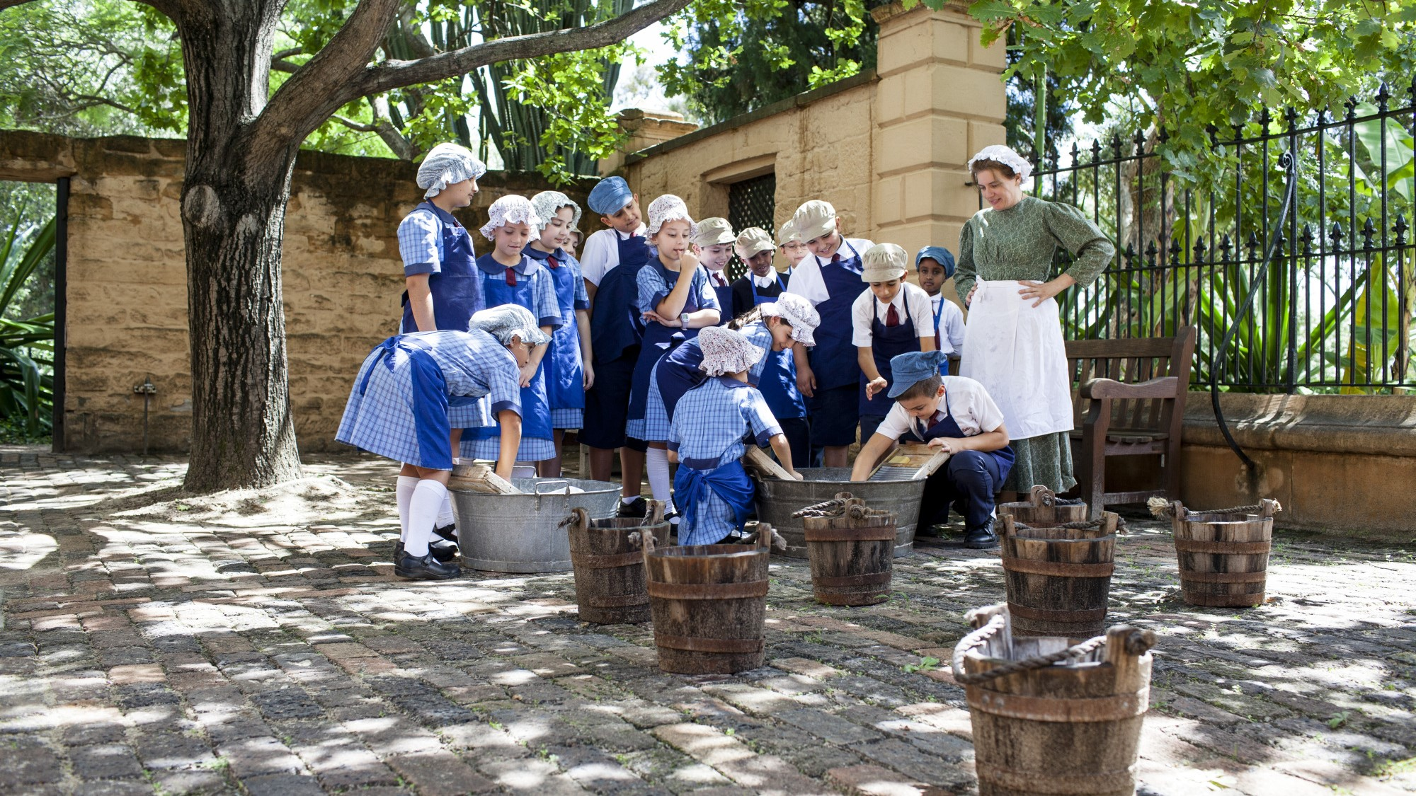 Students dressed as convicts washing clothes in sunny courtyard.